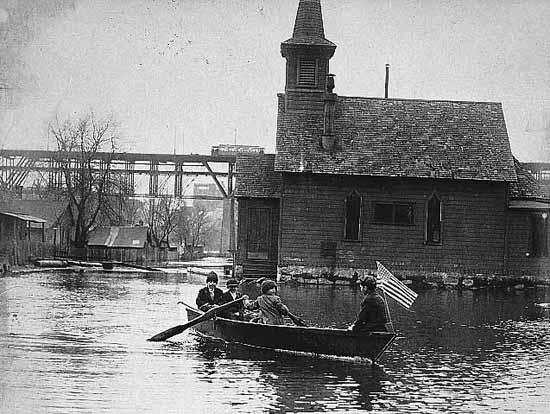 People in a rowboat, in front of a structure during a flood on the Bohemian Flats.