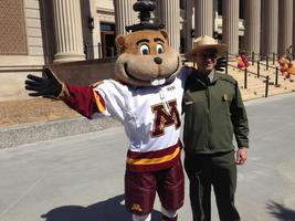 Goldy Gopher stands next to a National Park Service Ranger in front of Northrop Auditorium at the University of Minnesota.